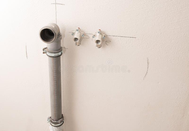 Vatten- och kloakinstallation, inre montering i en konstruktionsplats av ett bostads- hus, kopieringsutrymme royaltyfri bild