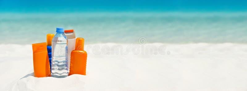 Vatten- och solskydd lagar mat med grädde på stranden royaltyfria bilder