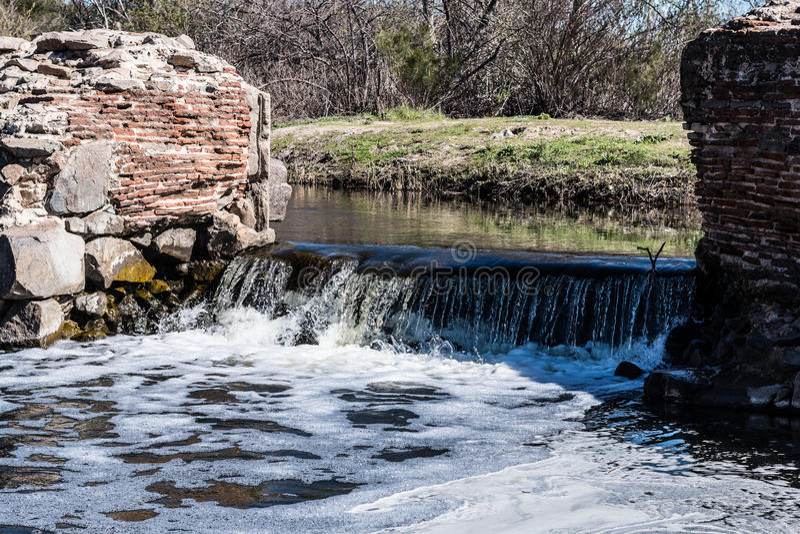 Vatten som flödar över vattenfallet på den gamla beskickningfördämningen arkivfoton