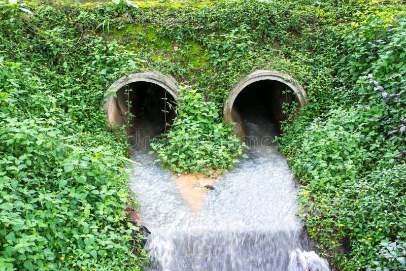 Vatten som flödar från avrinningröret in i en flod royaltyfri fotografi