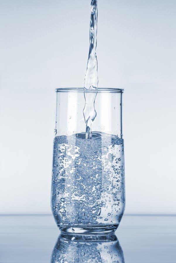Vatten som häller i exponeringsglas arkivbilder