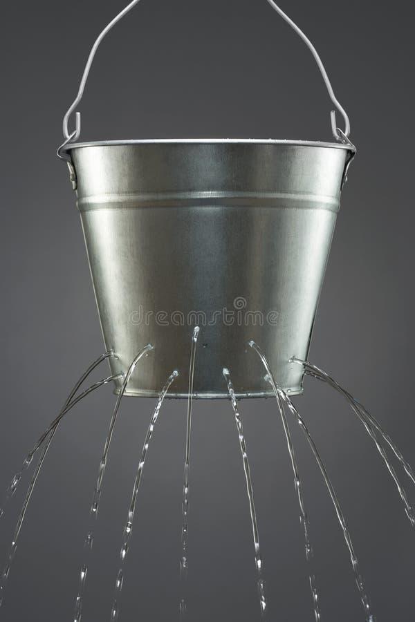 Vatten som läcker från hinken fotografering för bildbyråer