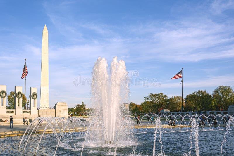 Vatten som plaskar från springbrunnen på minnesmärken för världskrig II med Washington Monument i bakgrunden i National Mall arkivfoton