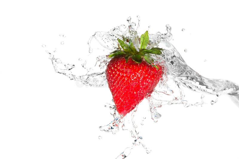 Vatten som plaskar på en jordgubbe royaltyfri fotografi