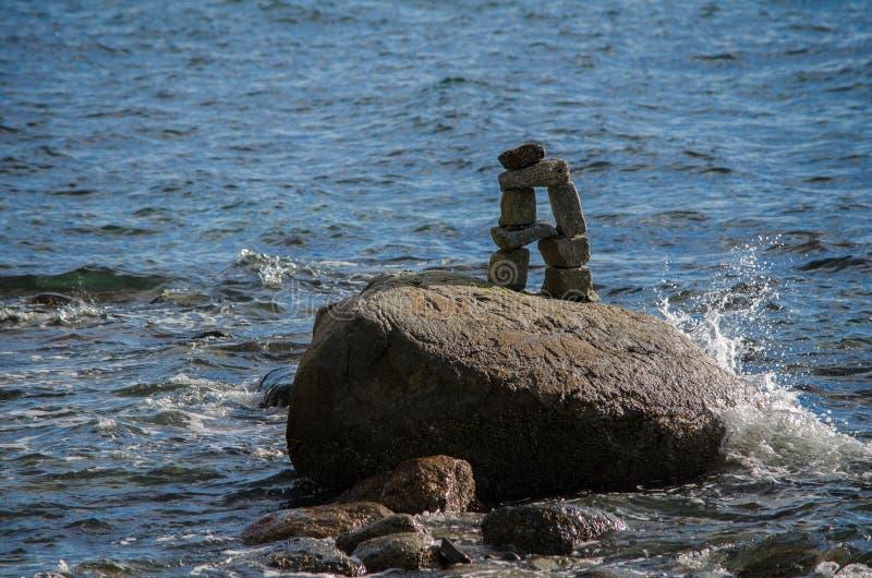 Vatten som plaskar upp på en Inuksuk i Stanley Park royaltyfria bilder