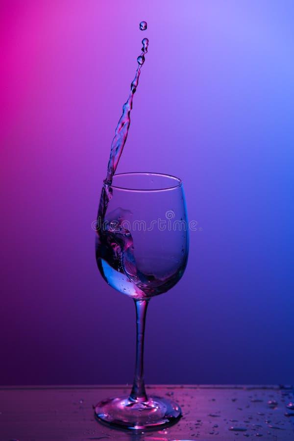 Vatten som plaskar ut ur ett vinexponeringsglas royaltyfri bild