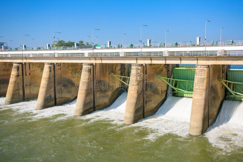 Vatten som rusar till och med portar på en fördämning arkivbild