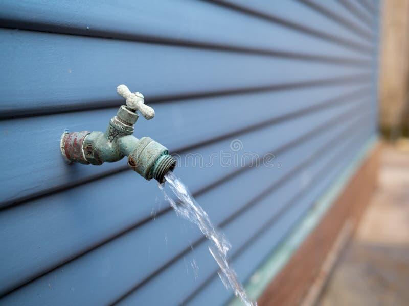 Vatten som utomhus strömmar ut ur den utomhus- vattenkranen för trädgårdslang royaltyfri bild