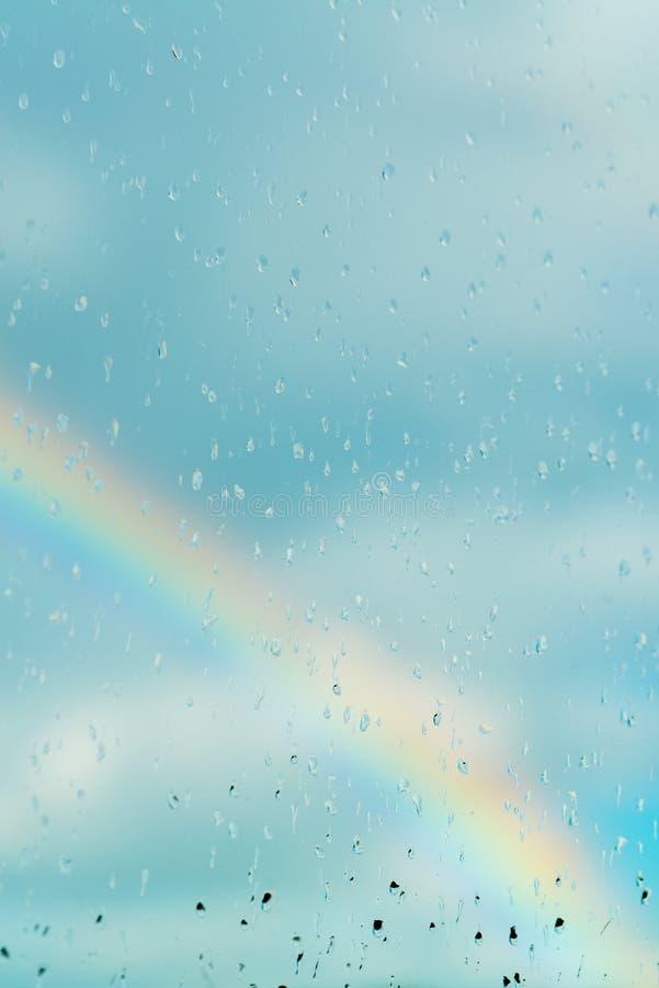 Vatten tappar på ett fönster med regnbågen i bakgrunden arkivbild