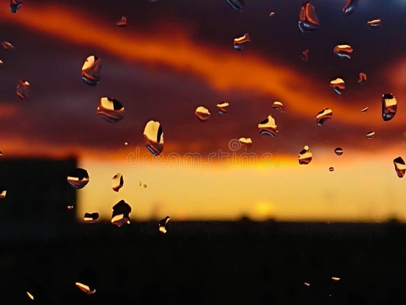 Vatten tappar på ett fönsterexponeringsglas efter regnet under solnedgången Rika himmel- och solfärger för closeupeyedroppers hög royaltyfri bild