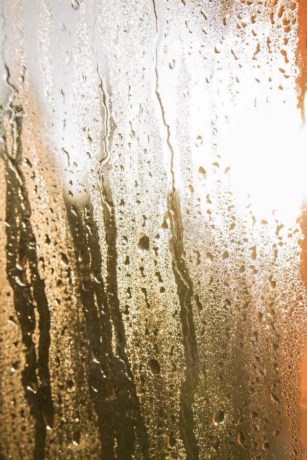 Vatten tappar på guling-, gräsplan- och apelsinexponeringsglas, regnsmå droppar på glass bakgrund royaltyfria bilder