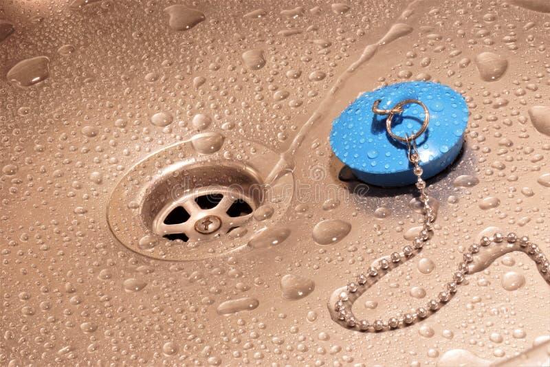 Vattenavrinning, droppar på vasken och avrinningpropp royaltyfria foton