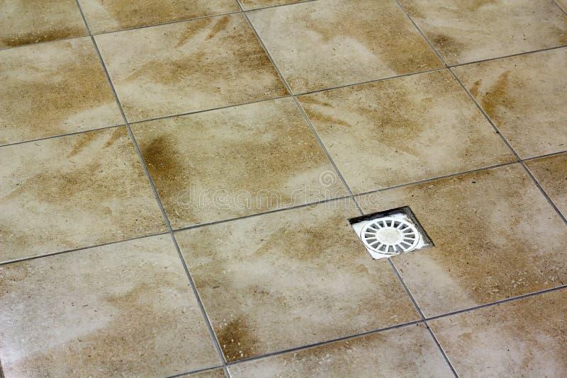 Vattenavrinninglufthål i keramiskt belagt med tegel gammalt tappninggolv för kök, för badrum eller för källare Geometrisk abstrak royaltyfri foto