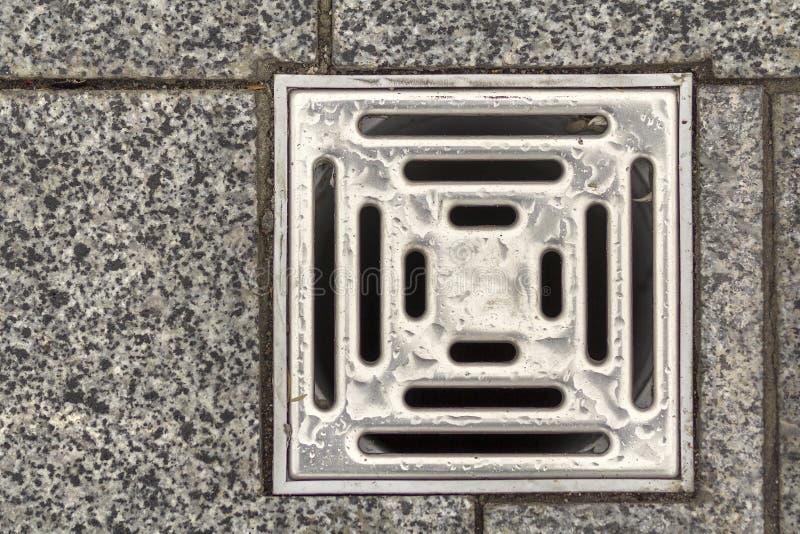 Vattenavrinninglufthål i keramiskt belagt med tegel gammalt tappninggolv för kök, för badrum eller för källare Geometrisk abstrak royaltyfria bilder