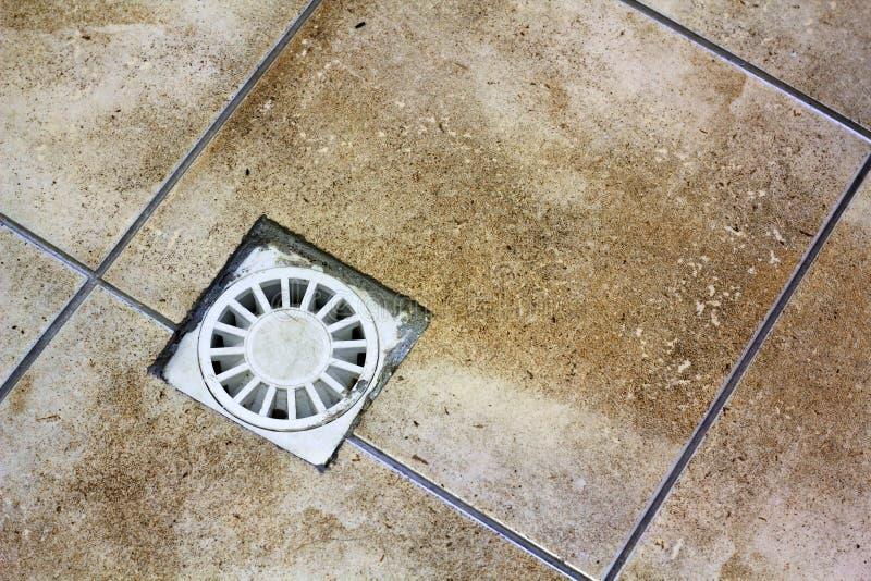 Vattenavrinninglufthål i keramiskt belagt med tegel gammalt tappninggolv för kök, för badrum eller för källare Geometrisk abstrak arkivbilder