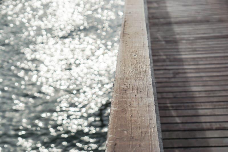 Vattenbrusande på träbron på flodstranden royaltyfri bild