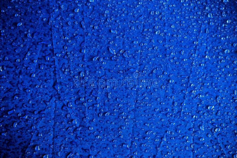 Vattendroppar i den blå vävnaden vattenfall på blå royaltyfri bild