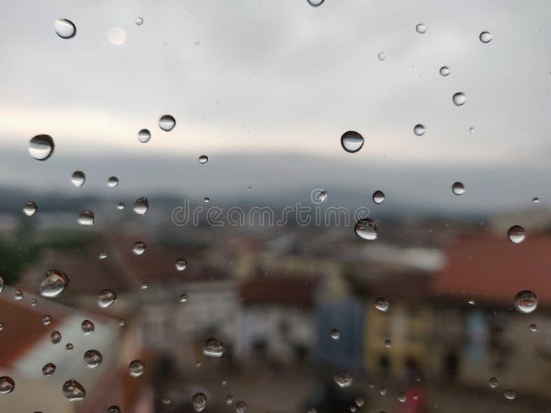 Vattendroppar i fönsterglas med staden Barcelona i bakgrunden arkivfoton