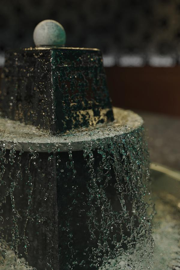 Vattendroppar på den inomhus springbrunnen för naturlig sten med den roterande bollen royaltyfri foto
