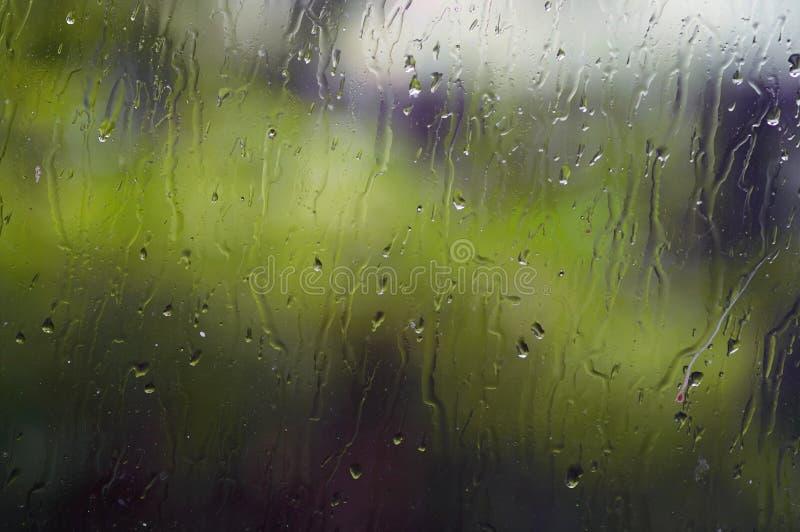 Vattendroppar på fönstret - plaskat exponeringsglas arkivfoto