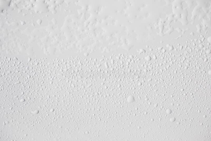 Vattendroppar stänger sig upp på det vita brädet arkivbild
