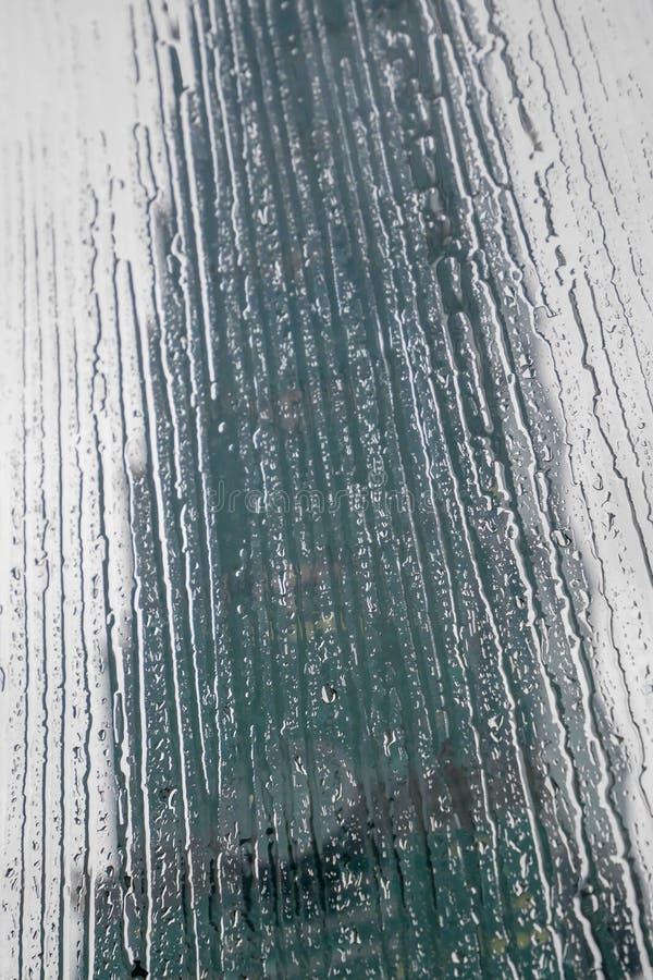 Vattendroppbakgrunder med lilla droppen p? exponeringsglas arkivbild