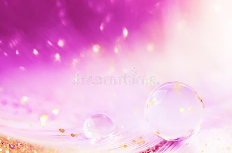 Vattendroppe, den genomskinlig bubblan och guld- blänker på fjäderbakgrund Härlig konstnärlig bild som tonas i rosa färg med gnis arkivfoto