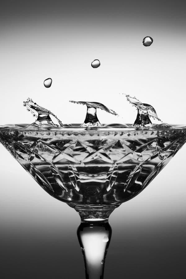 Vattendroppfärgstänk som skapar former i ett exponeringsglas royaltyfri foto