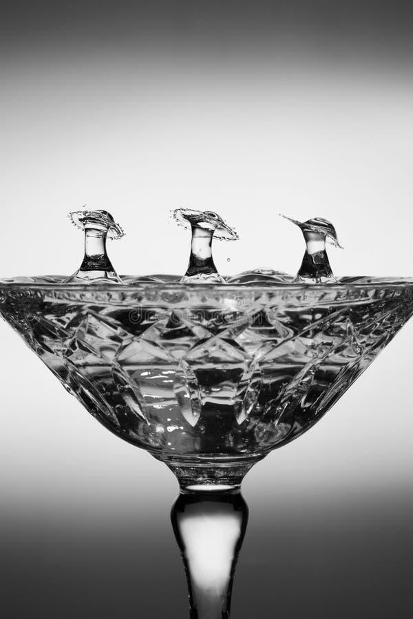Vattendroppfärgstänk som skapar former i ett exponeringsglas arkivfoton