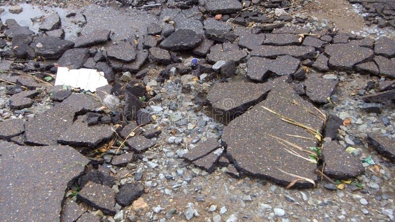 Vattenerosion av vägen Broken asfaltbakgrund Farahål, grå bakgrund för sten royaltyfria foton