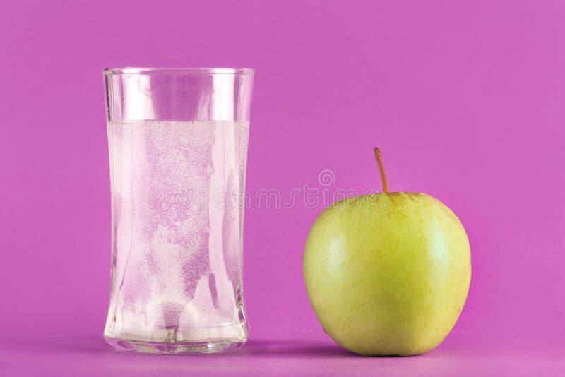 Vattenexponeringsglas med brustabletten med bubblor och det gröna äpplet fotografering för bildbyråer