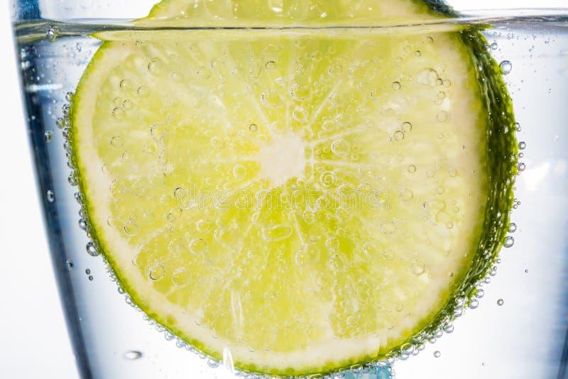 Vattenexponeringsglas och limefrukt fotografering för bildbyråer