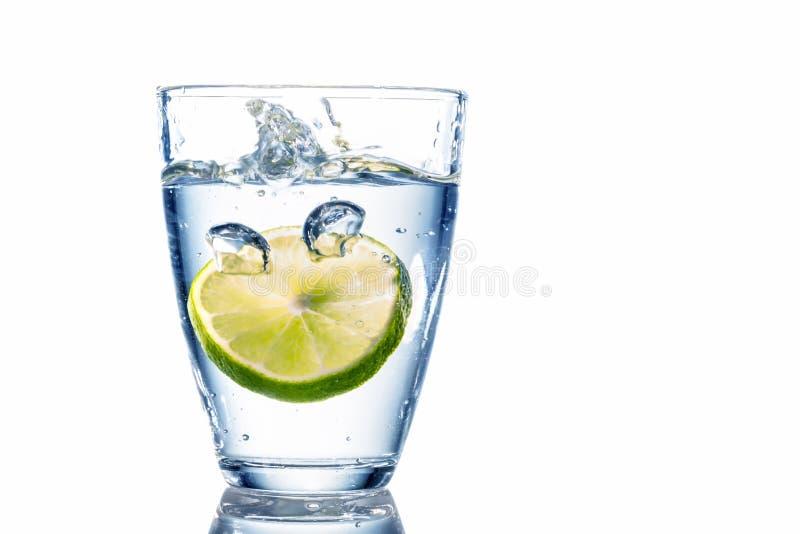 Vattenexponeringsglas och limefrukt arkivfoton