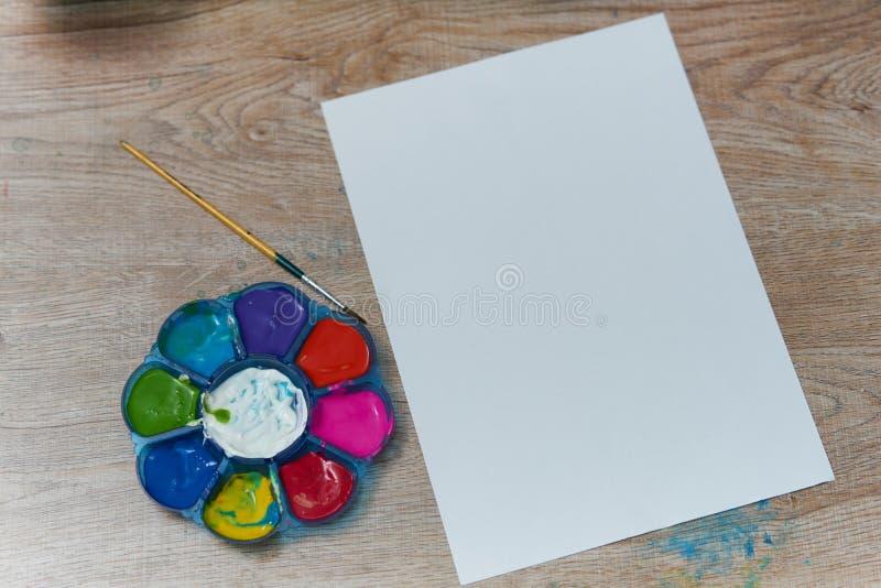 Vattenfärg med målarpenseln och vitt vanligt papper royaltyfri foto