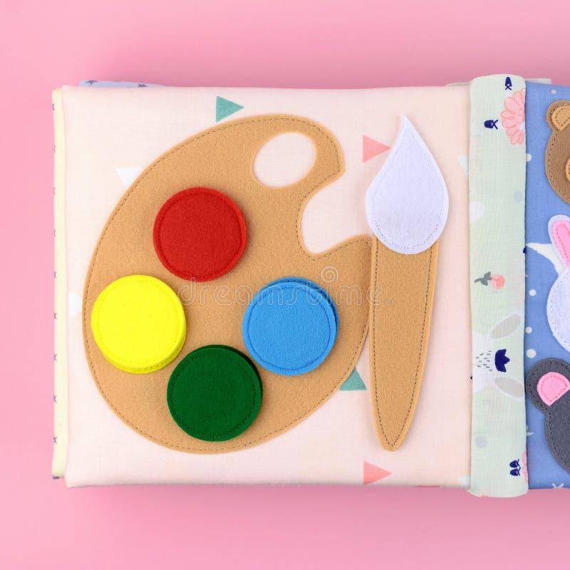 Vattenfärgmålarfärg från filt i en textilbok arkivbilder