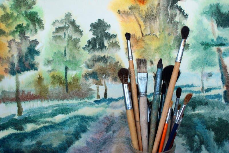 Vattenfärgmålarfärgborstar mot aquarellebakgrund arkivfoton