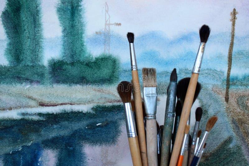 Vattenfärgmålarfärgborstar mot aquarellebakgrund arkivbilder