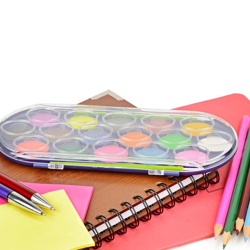 Vattenfärgmålarfärger, anteckningsböcker och andra skolatillförsel som isoleras på vit bakgrund Fritt avstånd för text arkivfoton