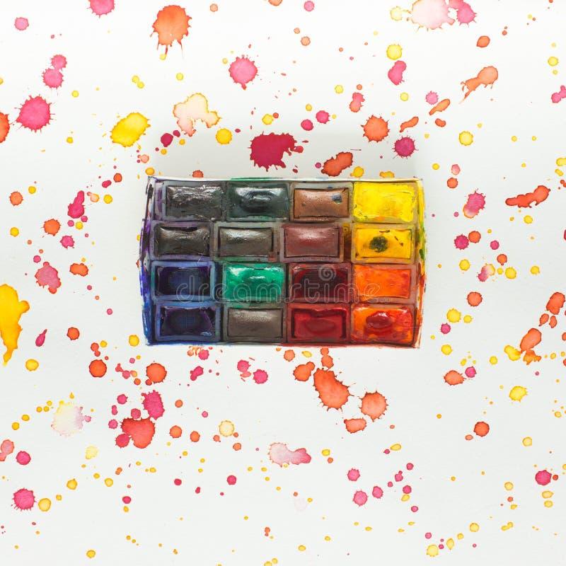 Vattenfärgmålarfärger, borstar och palett på den färgrika bakgrunden arkivfoton