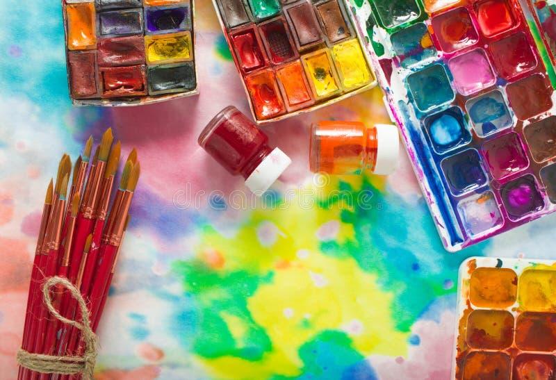 Vattenfärgmålarfärger, borstar och palett på den färgrika bakgrunden arkivbild