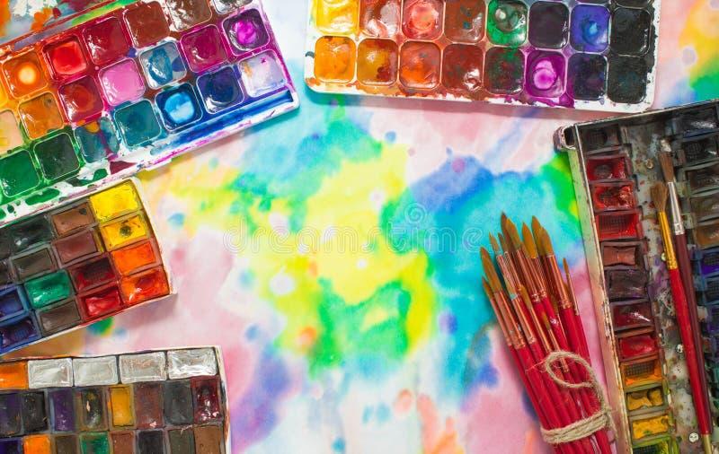 Vattenfärgmålarfärger, borstar och palett på den färgrika bakgrunden royaltyfri bild