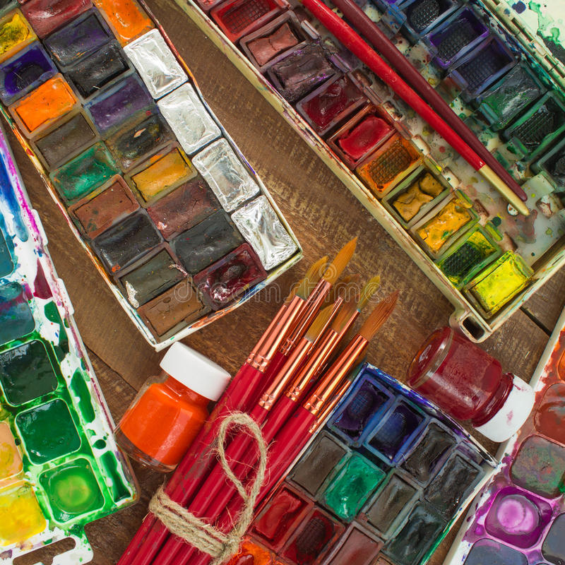 Vattenfärgmålarfärger, borstar och palett på en träbakgrund royaltyfria foton