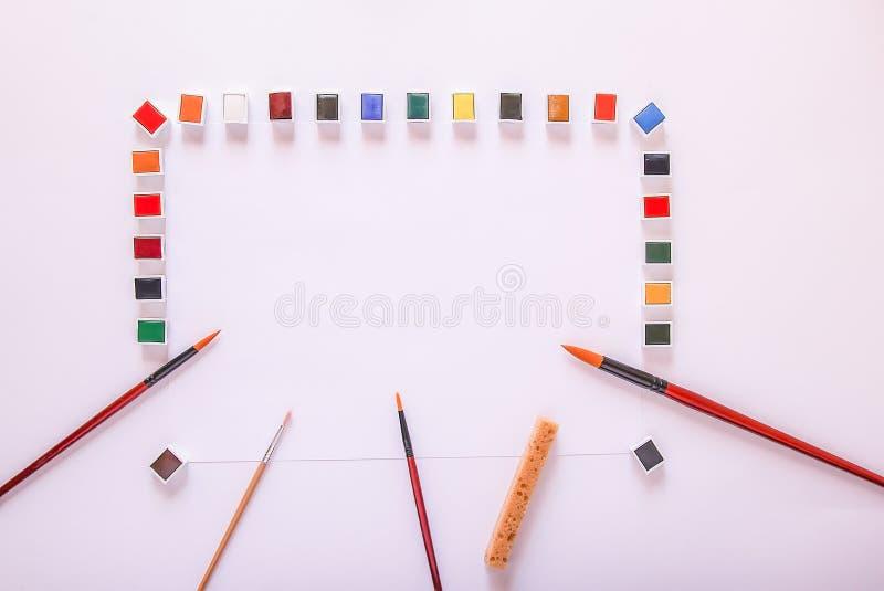 Vattenfärgmålarfärger, borstar och papper på vit bakgrund Lekmanna- l?genhet, b?sta sikt arkivbilder