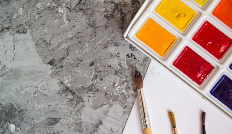Vattenfärgmålarfärger med borstar och papper på en konkret bakgrund royaltyfri foto