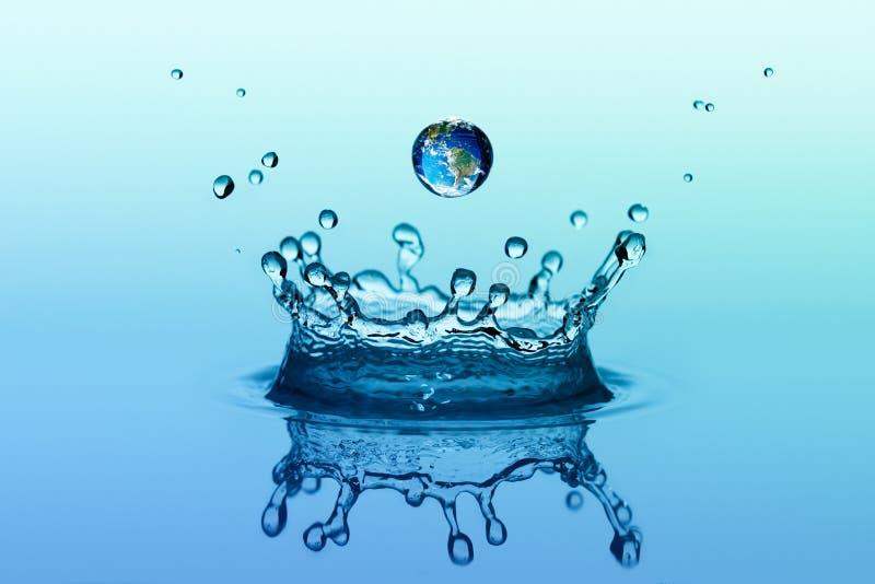 Vattenfärgstänk i kronaform och fallande droppe med jordbild royaltyfria bilder