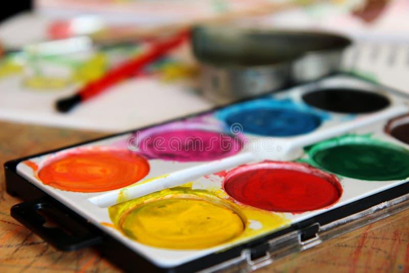 Vattenfärguppsättning för barn på tabellen fotografering för bildbyråer