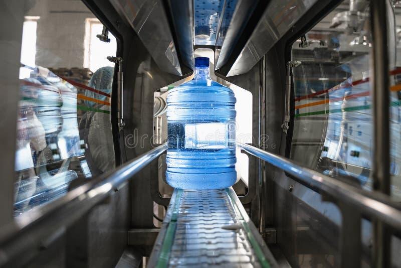 Vattenfabrik Burk eller gallon av plast med rent vatten inuti en automatisk transportörlina arkivbilder