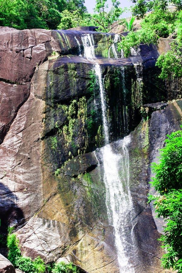 Vattenfall för sju brunnar i steniga berg och djungel på den tropiska ön royaltyfria bilder
