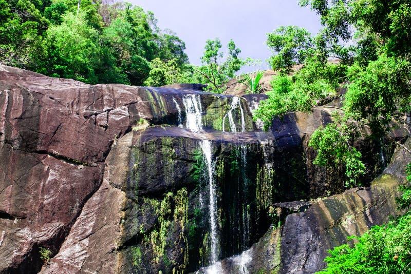 Vattenfall för sju brunnar i steniga berg och djungel på den tropiska ön royaltyfri fotografi
