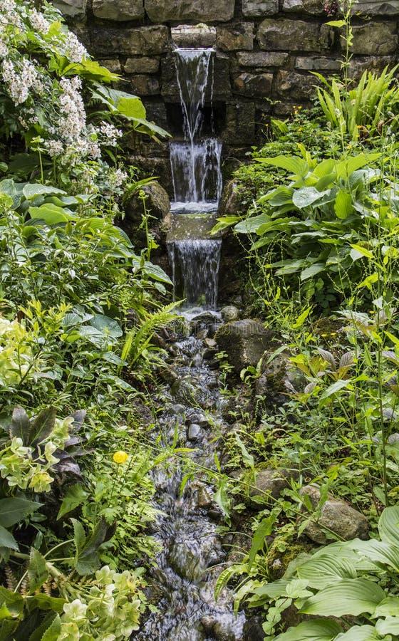 Vattenfall för tre etapp på formella trädgårdar på Anglesey, Wales, UK arkivfoto